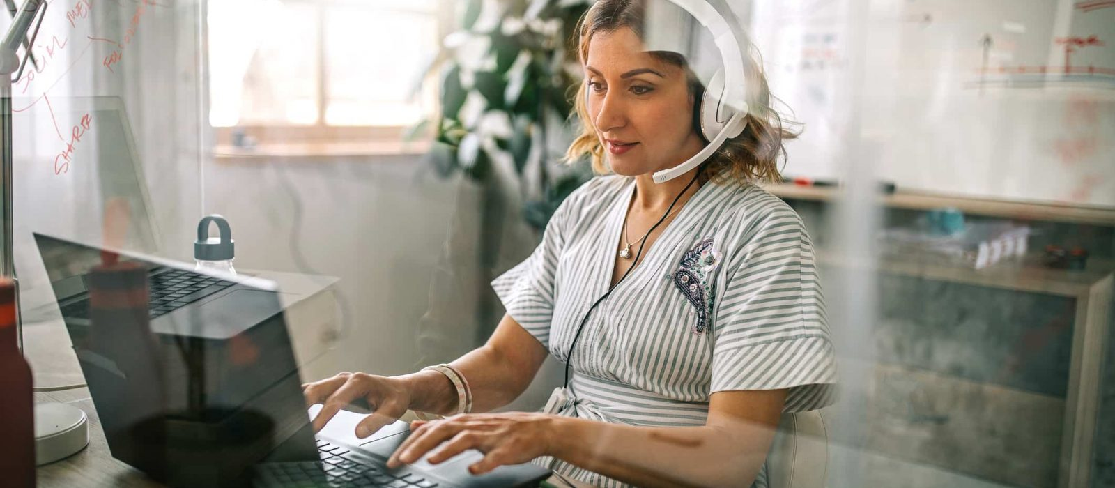 Businesswoman using laptop and headphones at office